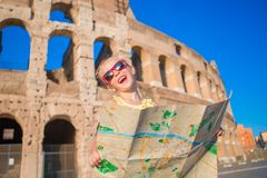 Adorable little active girl with map in front of Colosseum in Rome, Italy. Kid spending childhood in Europe Stock Images
