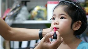 Adorable little Asian baby girl receiving a professional make up - applying lip paint using a small paint brush. Adorable little Asian baby girl, 36 months old stock footage