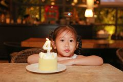 Adorable little Asian child girl with happy birthday cake 4 years old.  stock photo