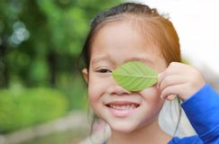 Adorable little Asian child girl holding a green leaf closing left eye in green garden background stock photos