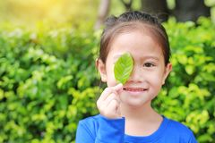 Adorable little Asian child girl holding a green leaf closing right eye in green garden background.  royalty free stock photos
