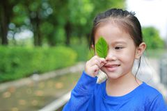 Adorable little Asian child girl holding a green leaf closing right eye in green garden background.  royalty free stock photography