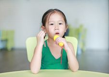 Adorable little Asian child girl sing a song by plastic microphone at the kid room.  stock image