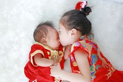 Adorable little asian girl kissing infant baby boy in cheongsam lying on white fur background during traditional chinese new year royalty free stock photos