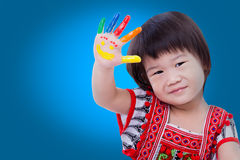 Adorable little asian (thai) girl painting her palm, on blue bac stock image