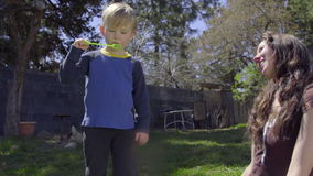Adorable little attempts to blow a bubble stock footage