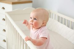 Adorable little baby with allergy in crib. At home stock image