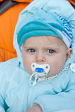 Adorable little baby in blue winter clothes. In orange stroller outdoors on sunny day Royalty Free Stock Images