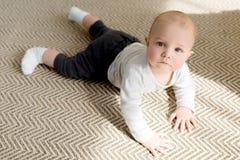 adorable little baby boy on floor looking stock photo