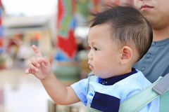 Adorable little baby boy pointing something with father carry by hipseat outdoor. Close up stock images