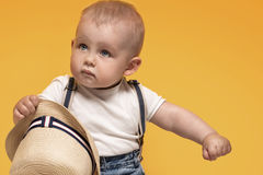 Adorable little baby boy posing. Cute baby boy posing in summer hat on yellow background. Adorable little child in studio stock images