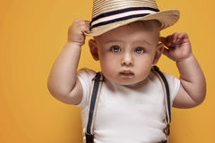 Adorable little baby boy posing. Cute baby boy posing in summer hat on yellow background. Adorable little child in studio stock photo