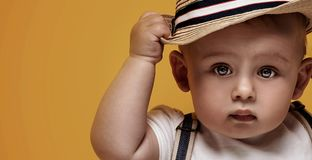 Adorable little baby boy posing. Cute baby boy posing in summer hat on yellow background. Adorable little child in studio royalty free stock photography