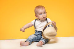 Adorable little baby boy posing. Cute baby boy posing in summer hat on yellow background. Adorable little child in studio royalty free stock photo