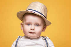 Adorable little baby boy posing. Cute baby boy posing in summer hat on yellow background. Adorable little child in studio stock photos