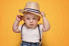 Adorable little baby boy posing. Cute baby boy posing in summer hat on yellow background. Adorable little child in studio royalty free stock image