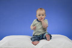 Adorable little baby boy, sitting on the white blanket, studio shot, isolated on blue background Stock Photo