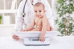 Adorable little baby child with pediatrician, weight measuring Stock Photo