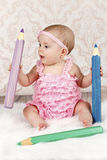 Adorable little baby girl with big crayons Royalty Free Stock Photos