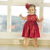 Adorable little baby girl in dark red dress standing near window Royalty Free Stock Photos