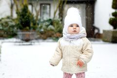 Adorable little baby girl making first steps outdoors in winter. Cute toddler learning walking. Child having fun on cold stock photography