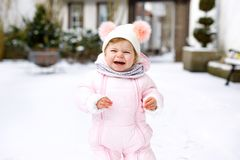 Adorable little baby girl making first steps outdoors in winter. Cute toddler learning walking. stock photography