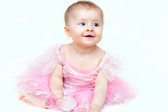 Adorable little baby girl in pink dress playing with her pink shoe Royalty Free Stock Photo
