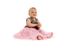 Adorable little baby girl in pink dress sitting on floor Royalty Free Stock Image