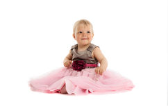 Adorable little baby girl in pink dress sitting on floor Royalty Free Stock Images