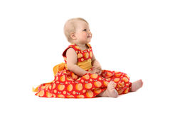 Adorable little baby girl in red dress sitting on floor Royalty Free Stock Images