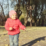 Adorable little baby girl walking in the autumn park Royalty Free Stock Photos