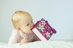 Adorable little baby lying on the white blanket and holding purple gift bag in his hands. Horisontal studio shot. Happy stock photo