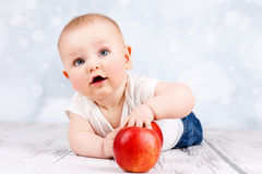 Adorable little baby playing with apples. Studio portrait of cute and funny toddler Stock Photo
