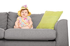 Adorable little baby seated on a couch Royalty Free Stock Image