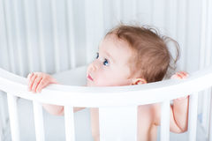 Adorable little baby standing in round white crib Royalty Free Stock Images