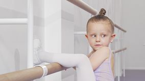 Adorable little ballerina girl putting her leg on ballet bar for stretching. Happy little girl in leotard exercising at ballet school, stretching her leg on stock footage
