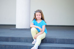 Adorable little beautiful girl sitting on a stairway stock photo