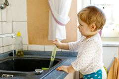 Adorable little blond baby girl washing dishes in domestic kitchen. Happy child having fun with helping with house work. Indoors, toddler in colorful clothes Stock Photos