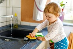 Adorable little blond baby girl washing dishes in domestic kitchen. Happy child having fun with helping with house work. Indoors, toddler in colorful clothes Royalty Free Stock Image