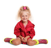 Adorable little blond girl in jacket, rubber boots sitting isolated. Royalty Free Stock Photo