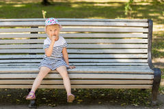 Adorable little blond girl sitting on a bench in a city park and eating cone ice-cream Stock Photo