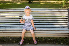 Adorable little blond girl sitting on a bench in a city park and eating cone ice-cream Stock Photography