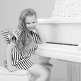 Adorable little blond girl in very short summer striped dress. She sits on a chair near a white piano.Black and white photography Stock Photos
