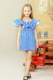 Adorable little blond girl in very short summer striped dress. Royalty Free Stock Photo