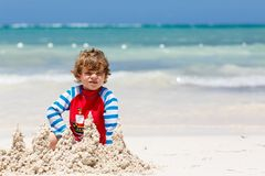 Adorable little blond kid boy having fun on tropical beach of carribean island. Excited child playing and building sand royalty free stock image