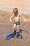 Adorable little blond kid boy having fun on tropical beach. Excited child playing and surfing  sun protected swimsuit in ocean o Royalty Free Stock Image