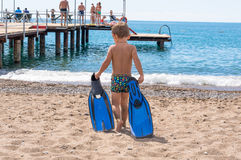 Adorable little blond kid boy having fun on tropical beach. Excited child playing and surfing in sun protected swimsuit  ocean o Stock Images