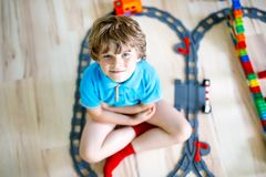 Little blond kid boy playing with colorful plastic blocks and creating train station. Adorable little blond kid boy playing with colorful plastic blocks and Royalty Free Stock Photos