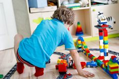 Little blond kid boy playing with colorful plastic blocks and creating train station. Adorable little blond kid boy playing with colorful plastic blocks and Stock Photos