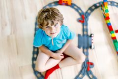 Little blond kid boy playing with colorful plastic blocks and creating train station. Adorable little blond kid boy playing with colorful plastic blocks and Royalty Free Stock Image